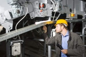 A maintenance engineer at work tightening bolts of an industrial appliance