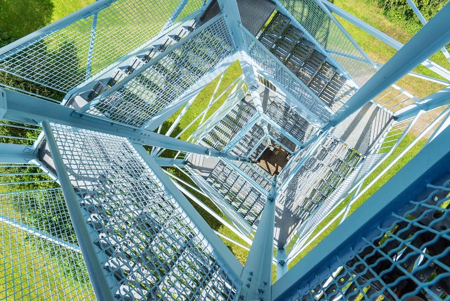 View from above through the open stairway of a light blue metal tower