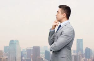 business and people concept - thinking businessman in suit making decision over city background